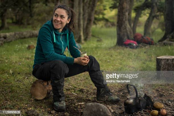 Chilean woman drinks yerba mate tea while camping