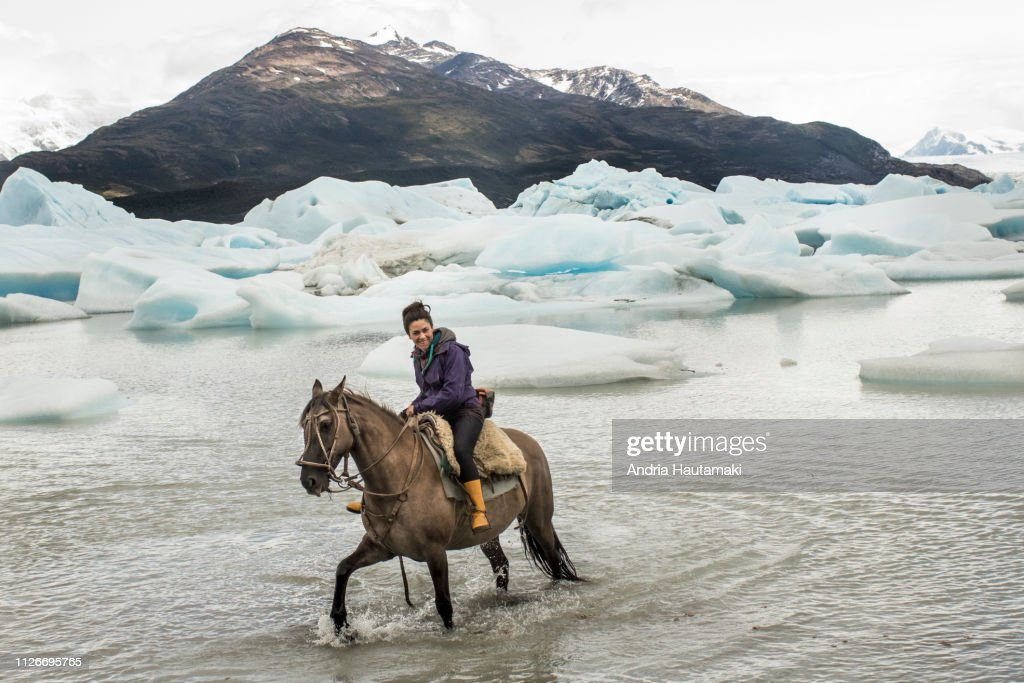 Chilean woman rides a horse in glacial lake : Stock-Foto