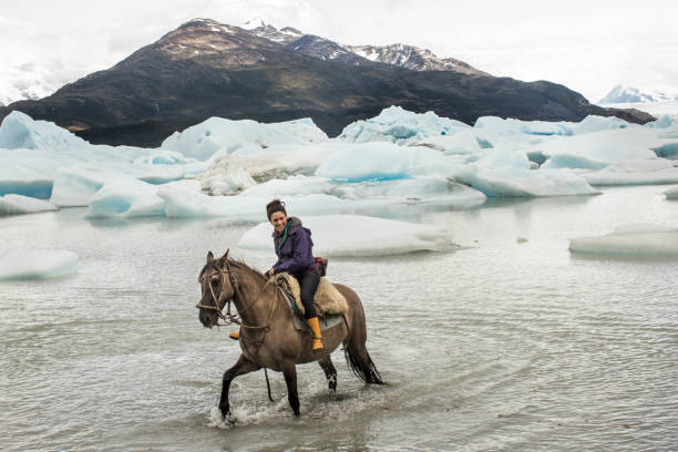 Chilean woman rides a horse in glacial lake
