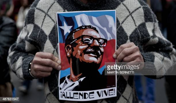 A chilean worker shows a poster despicting late Chilean President Salvador Allende as he takes part in the May Day parade organized by the Chilean...
