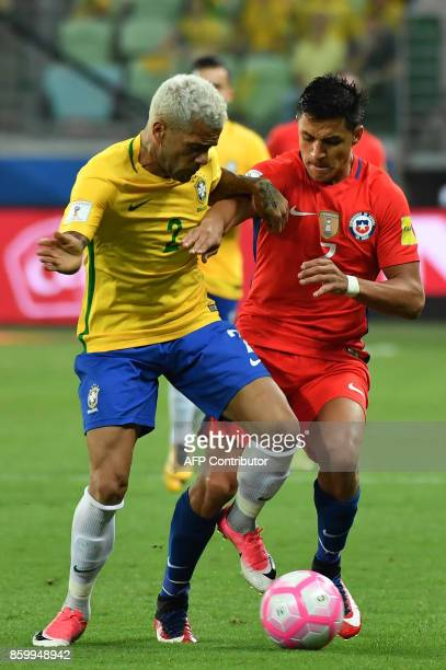 Chile's Alexis Sanchez and Brazil's Dani Alves vie for the ball during their 2018 World Cup football qualifier match in Sao Paulo Brazil on October...