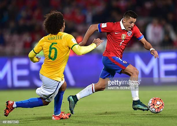 Chile's Alexis Sanchez drives the ball past Brazil's Marcelo during their Russia 2018 FIFA World Cup qualifiers match at the Nacional stadium in...