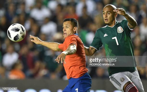 Chile's Alexis Sanchez vies for the ball with Luis Rodriguez of Mexico during their friendly football match at the La Corregidora stadium in...