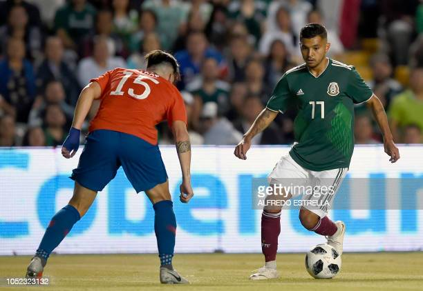 Chile's Alfonso Parot vies for the ball with Mexico's Isaac Brizuela during their friendly football match at the La Corregidora stadium in Queretaro...