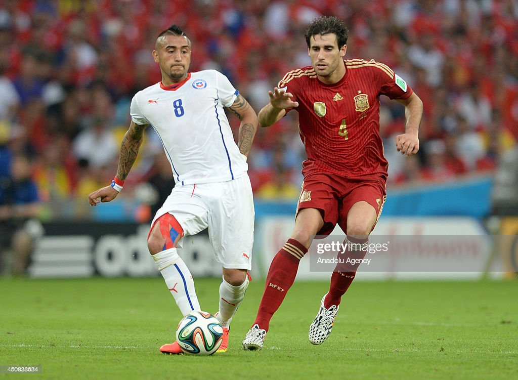 Chile's Artura Vidal (8) vies for the ball with Javi Martinez (4) of Spain during the 2014 FIFA World Cup Group B soccer match between Spain and Chile at the Maracana Stadium in Rio de Janeiro, Brazil, on June 18, 2014.