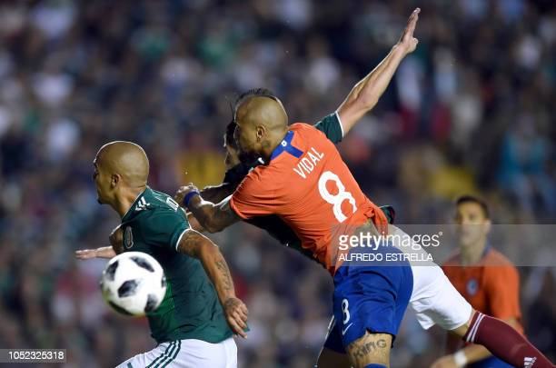 Chile's Arturo Vidal vies for the ball with Mexico's Luis Rodriguez during their friendly football match at the La Corregidora stadium in Queretaro...