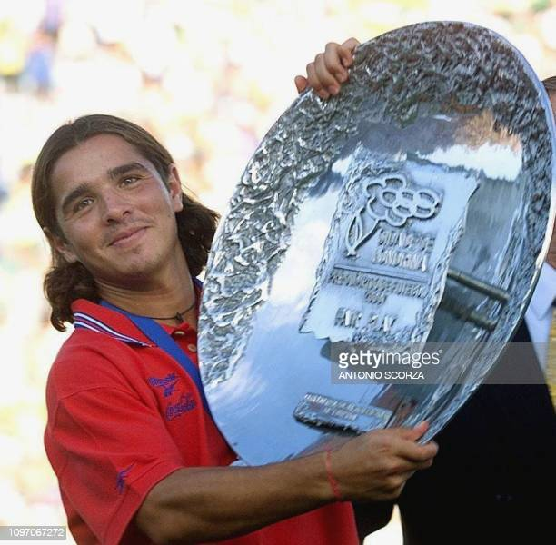 Chile's captain Hector Tapia holds the trophy for the second place qualifier in the Sydney 2000 soccer qualification tournament 06 February in...