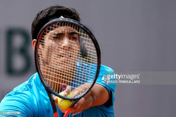 Chile's Christian Garin prepares to serve to Reilly Opelka of the US during their men's singles first round match on day two of The Roland Garros...