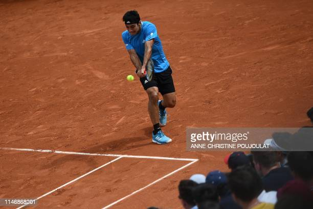 Chile's Christian Garin returns the ball to Switzerland's Stanislas Wawrinka during their men's singles second round match on day four of The Roland...