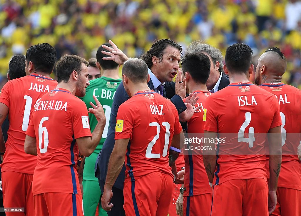 TOPSHOT - Chile's coach Juan Antonio Pizzi (C) talks to the players during the 2018 FIFA World Cup qualifier football match against Colombia in Barranquilla, on November 10, 2016. / AFP / Luis Acosta