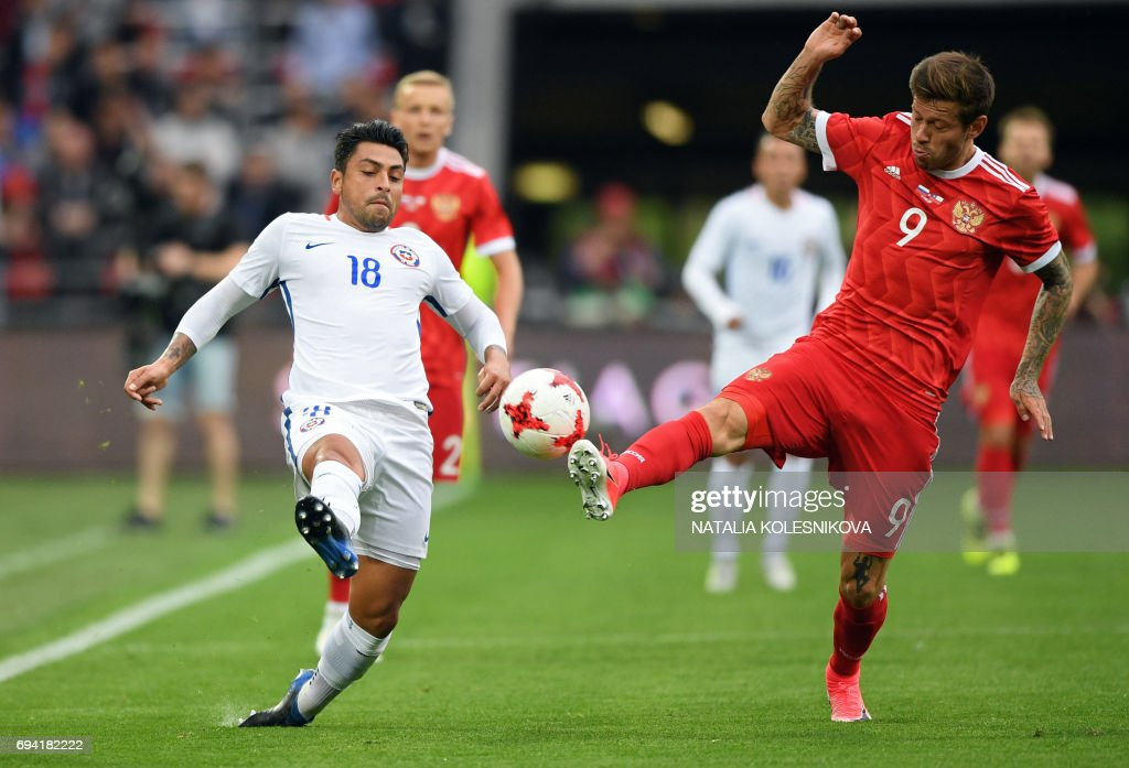 Chile's defender Gonzalo Jara (L) and Russia's forward Fedor Smolov vie for the ball during a friendly football match between Russia and Chile at the CSKA Arena in Moscow on June 9, 2017. / AFP PHOTO / Natalia KOLESNIKOVA