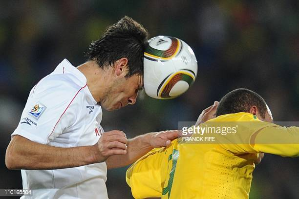 Chile's defender Ismael Fuentes heads the ball next to Brazil's striker Luis Fabiano during the 2010 World Cup round of 16 football match Brazil...