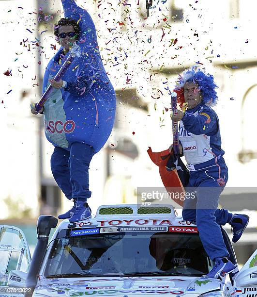 Chile's driver Jorge Latrach and codriver Juan Latrach joke atop their Toyota on the podium of the symbolic start of the Dakar 2011 Rally in downtown...
