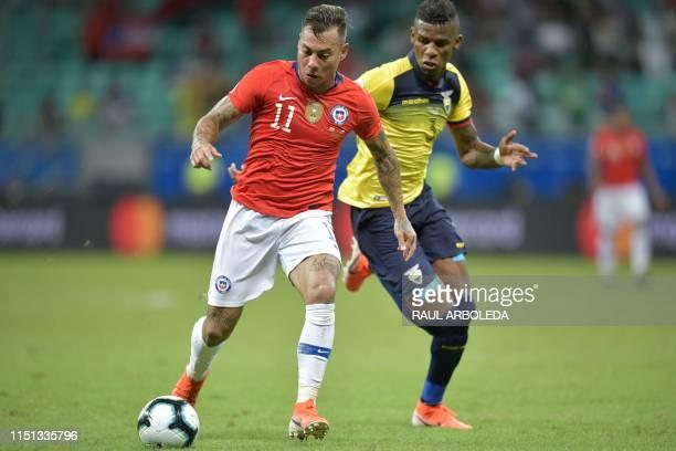 Chile's Eduardo Vargas and Ecuador's Gabriel Achilier vie for the ball during their Copa America football tournament group match at the Fonte Nova...