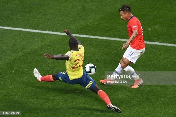 Chile's Eduardo Vargas is marked by Colombia's Davinson Sanchez as he aims at the goal during their Copa America football tournament quarterfinal...