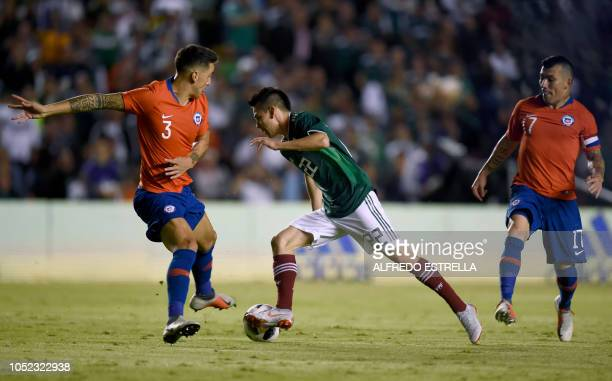 Chile's Enzo Roco and Gary Medel vie for the ball with Mexico's Hirving Lozano during their friendly football match at the La Corregidora stadium in...