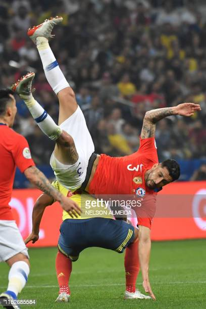 Chile's Erick Pulgar falls next to Colombia's Roger Martinez during their Copa America football tournament quarterfinal match at the Corinthians...