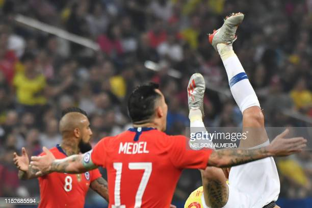 Chile's Erick Pulgar falls next to teammates Chile's Arturo Vidal and Gary Medel during their Copa America football tournament quarterfinal match at...