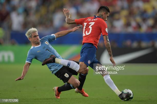 Chile's Erick Pulgar is marked by Uruguay's Nicolas Lodeiro during their Copa America football tournament group match at Maracana Stadium in Rio de...