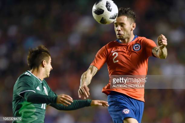 Chile's Eugenio Mena heads the ball next to Mexico's Isaac Brizuela during the friendly football match between Mexico and Chile at the La Corregidora...