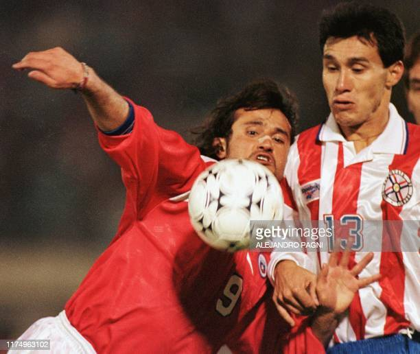 Chile's Fernando Vergara and Paraguay's Jorge Alcaraz fight for the ball 11 June during the inaugural match of the Copa America soccer tournament in...
