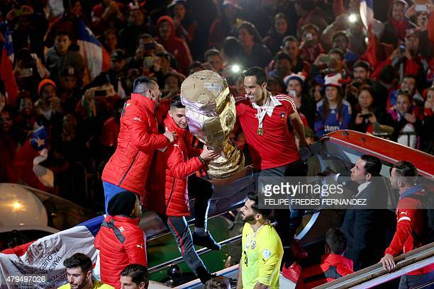Chile's football team players show the trophy to the crowd from the bus that takes them to La Moneda presidential palace in Santiago on July 4 2015...