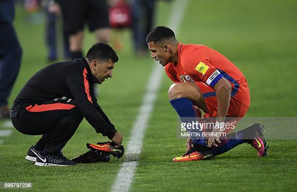 Chile's forward Alexis Sanchez changes his boots during the Russia 2018 World Cup football qualifier match against Bolivia in Santiago on September 6...