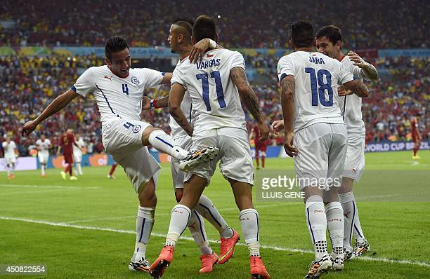 Chile's forward Eduardo Vargas celebrates scoring with his teammates during a Group B football match between Spain and Chile in the Maracana Stadium...