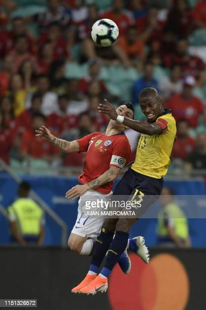 Chile's Gary Medel and Ecuador's Enner Valencia jump for the ball during their Copa America football tournament group match at the Fonte Nova Arena...
