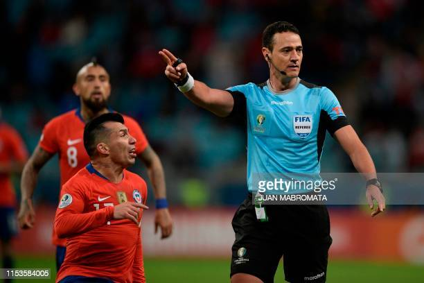 Chile's Gary Medel talks to Colombian referee Wilmar Roldan during the Copa America football tournament semifinal match against Peru at the Gremio...