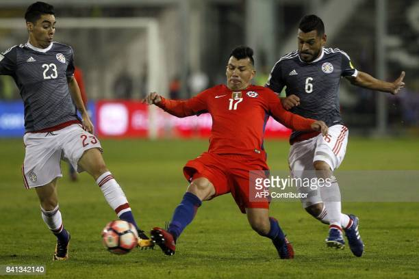Chile's Gary Medel vies for the ball with Paraguay's Miguel Almiron and Miguel Samudio during their 2018 World Cup qualifier football match in...
