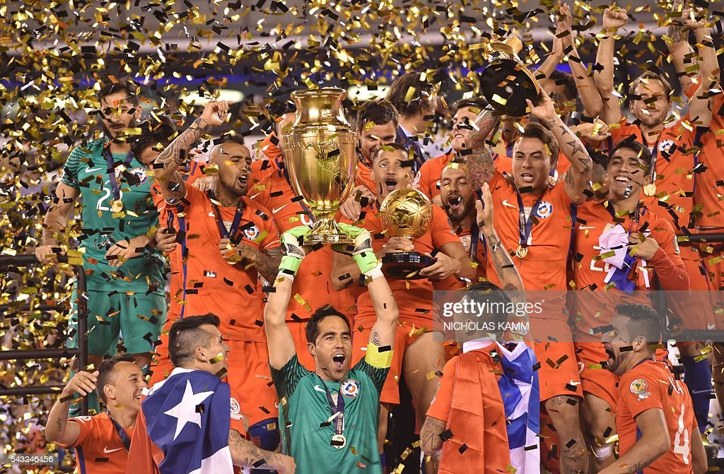 Chile's goalkeeper Claudio Bravo holds the trophy after winning the Copa America Centenario final by defeating Argentina in the penalty shoot-out in East Rutherford, New Jersey, United States, on June 26, 2016. / AFP / Nicholas Kamm