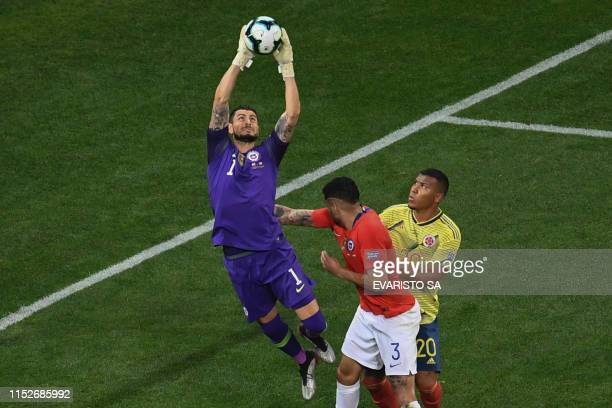 Chile's goalkeeper Gabriel Arias traps the ball next to teammate Guillermo Maripan and Colombia's Roger Martinez during their Copa America football...