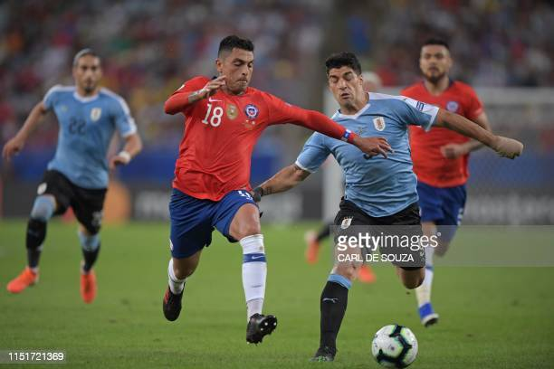 Chile's Gonzalo Jara and Uruguay's Luis Suarez vie for the ball during their Copa America football tournament group match at Maracana Stadium in Rio...