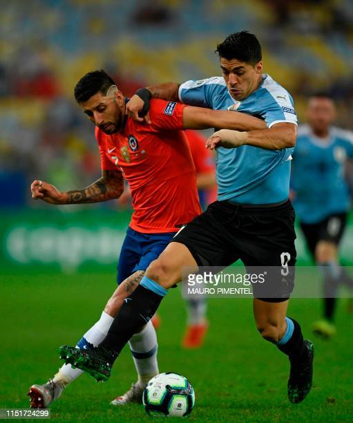 Chile's Guillermo Maripan and Uruguay's Luis Suarez ie for the ball during their Copa America football tournament group match at Maracana Stadium in...