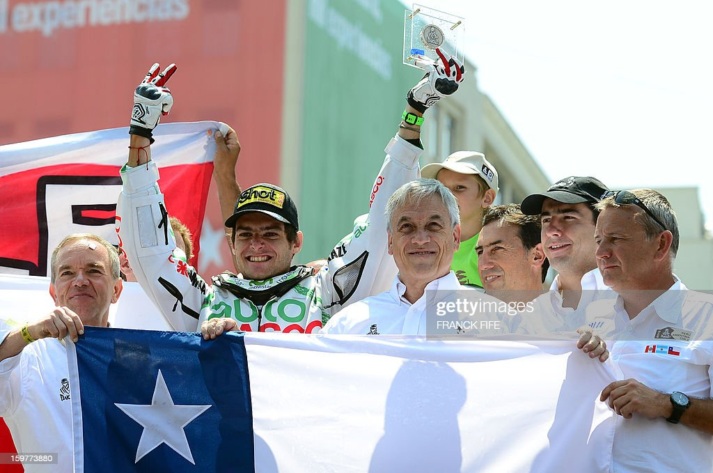 Chile's Ignacio Casale (L) reacts next to Chile's president Sebastian Pinera (R) and the director of the Dakar Rally 2010 Etienne Lavigne (R) on the podium of the Dakar 2013 in Santiago, Chile on January 20, 2013. France's Cyril Despres won the Dakar 2013 ahead of Ktm's rider Ruben Faria of Portugal KTM?s rider Francisco Chaleco Lopez of Chile.