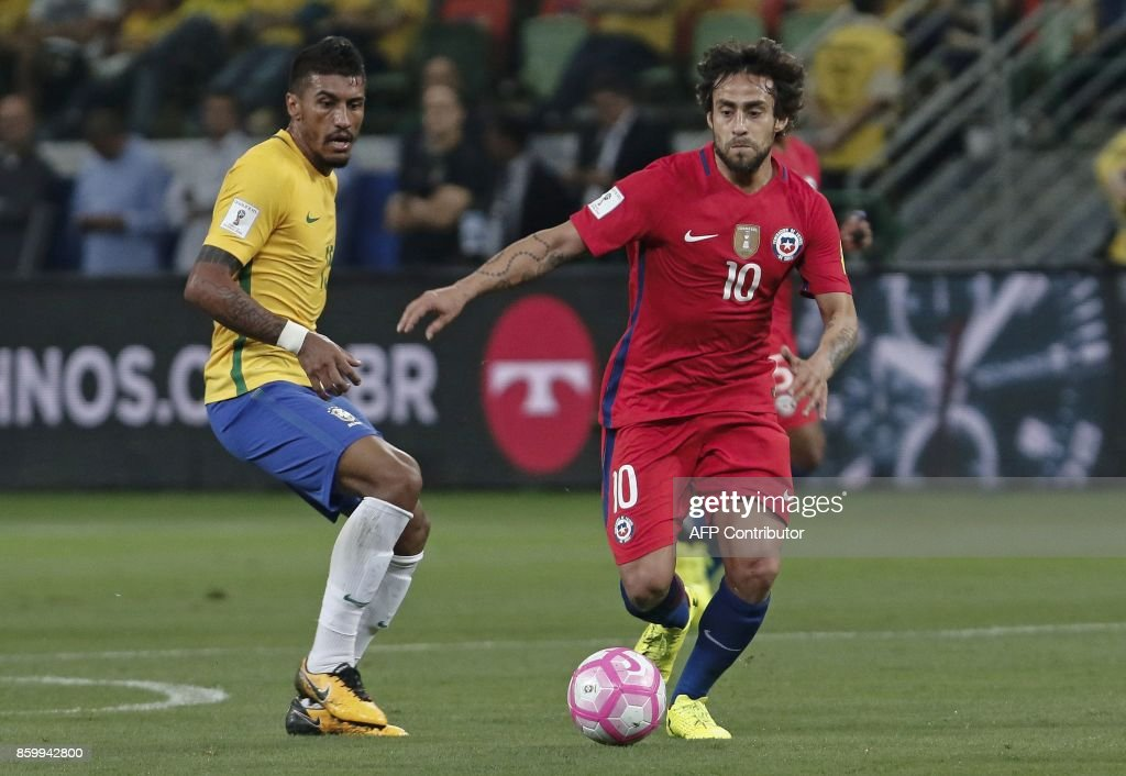 Chile's Jorge Valdivia (R) drives the ball past Brazil's Paulinho during their 2018 World Cup football qualifier match in Sao Paulo, Brazil, on October 10, 2017. / AFP PHOTO / Miguel SCHINCARIOL