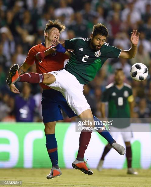 Chile's Mauricio Isla vies for the ball with Mexico's Nestor Araujo during the friendly football match between Mexico and Chile at the La Corregidora...