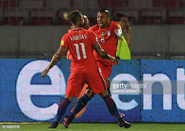 Chile's midfielder Arturo Vidal celebrates with teammate Chile's forward Eduardo Vargas after scoring against Peru during their Russia 2018 World Cup...