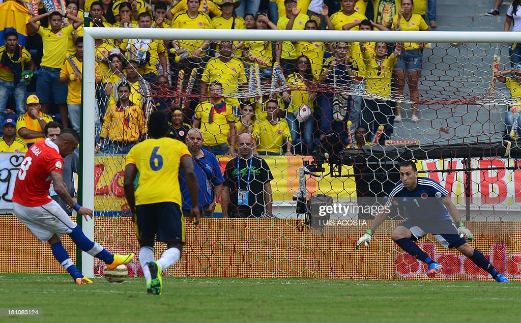 Chile's midfielder Arturo Vidal (L) takes a penalty kick against Colombia's goalkeeper David Ospina during their Brazil 2014 FIFA World Cup South American qualifier match, in Barranquilla, Colombia, on October 11, 2013.