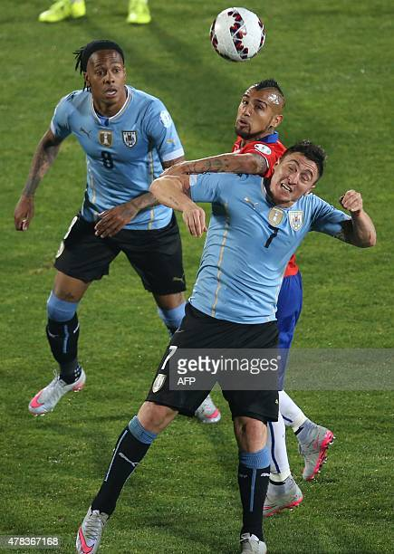 Chile's midfielder Arturo Vidal vies for the ball with Uruguay's forward Abel Hernandez and Uruguay's midfielder Cristian Rodriguez during their 2015...
