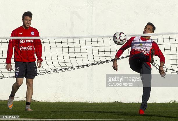 Chile's national football team striker Alexis Sanchez controls the ball next to Angelo Henriquez during a training session in Santiago on June 8 2015...