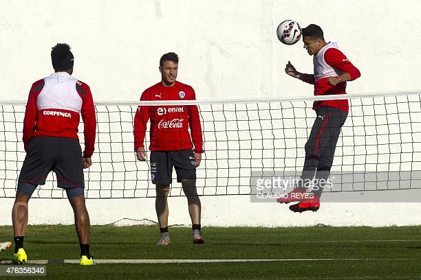 Chile's national football team striker Alexis Sanchez heads the ball next to Angelo Henriquez during a training session in Santiago on June 8 2015...