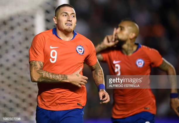 Chile's Nicolas Castillo celebrates his goal against Mexico with his teammate Arturo Vidal during the friendly football match between Mexico and...