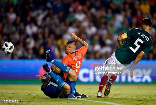 Chile's Nicolas Castillo scores a goal past Mexico's goalkeeper Hugo Gonzalez and Diego Reyes during the friendly football match between Mexico and...
