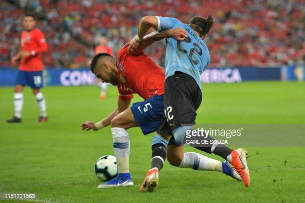 Chile's Paulo Diaz and Uruguay's Martin Caceres vie for the ball during their Copa America football tournament group match at Maracana Stadium in Rio...
