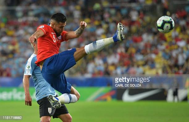 TOPSHOT Chile's Paulo Diaz strikes the ball during the Copa America football tournament group match against Uruguay at Maracana Stadium in Rio de...