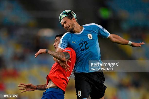 Chile's Pedro Pablo Hernandez and Uruguay's Martin Caceres jump for a header during their Copa America football tournament group match at Maracana...