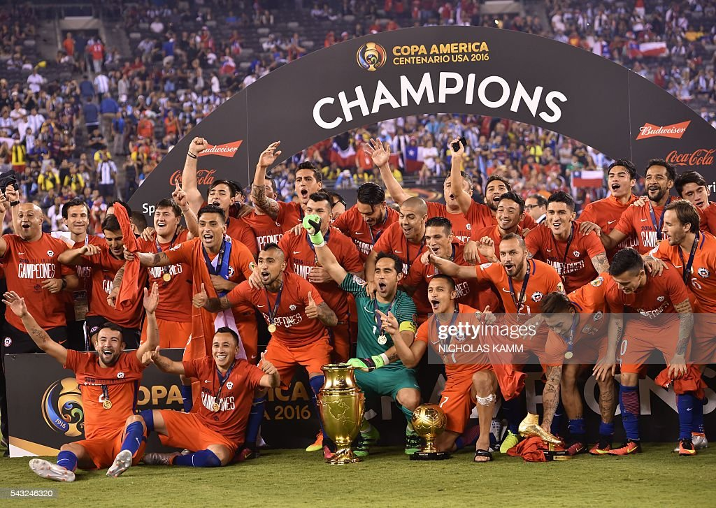 TOPSHOT - Chile's players pose with the trophy after winning the Copa America Centenario final by defeating Argentina in the penalty shoot-out in East Rutherford, New Jersey, United States, on June 26, 2016. / AFP / Nicholas Kamm