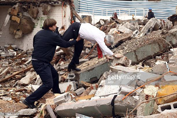 Chile's President Rafael Pinera stumbles and falls on the rubble during a visit to the demolition works of social housing in Bajos de Mena Puente...